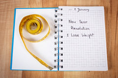 New years resolutions written in notebook and tape measure Royalty Free Stock Photos