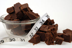 New Years Resolve. Resolving not to eat all this chocolate fudge is a good start. A white measuring tape wraps the chunks over a white background Stock Images