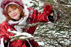 New years's woman. Woman dressed like santa claus near fir-tree Royalty Free Stock Photography