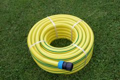 New yellow hose pipe in a garden. New yellow hose pipe on a grass in a garden stock images
