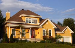 New yellow house. New yellow familial country house with deep blue sky and green lawn Stock Photo