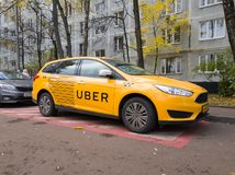 New yellow taxi with Uber logo and inscription at the street. Moscow, Russia - October 25, 2017: New yellow taxi with Uber logo and inscription at the street Royalty Free Stock Image