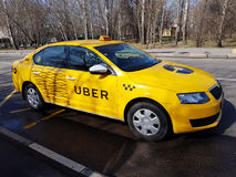 New yellow taxi with Uber logo. Moscow, Russia - April 11, 2017: New yellow taxi with Uber logo and inscription at the street royalty free stock photos