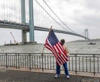 Flag-bearing spectator salutes on the Brooklyn shoreline as the USNS Comfort Hospital Ship departing New York City