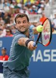 Professional tennis player Grigor Dimitrov of Bulgaria in action during his US Open 2017 second round match. NEW YORK - AUGUST 31, 2017: Professional tennis Stock Photography