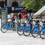 New York bicycle rental. NEW YORK, USA - JULY 4, 2013: People walk past Citibike bicycle sharing station in New York. WIth 330 stations and 6,000 bicycles it is Stock Photos