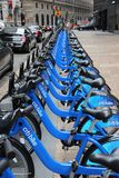 New York bicycle rental. NEW YORK, USA - JULY 2, 2013: Person walks by Citibike bicycle rental station in New York. With 330 stations and 6,000 bicycles it is Royalty Free Stock Photo