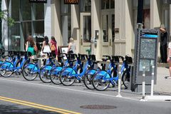 New York bicycle sharing. NEW YORK - JULY 2: People walk past Citibike bicycle sharing station on July 2, 2013 in New York. WIth 330 stations and 6,000 bicycles Royalty Free Stock Images