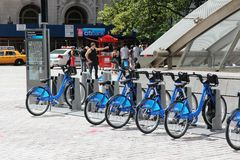 New York bicycles. NEW YORK - JULY 4: People walk past Citibike bicycle sharing station on July 4, 2013 in New York. WIth 330 stations and 6,000 bicycles it is Stock Image