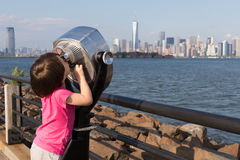 New York binoculars. Young girl attempting to use binoculars to view Hudson river and New York's lower Manhattan royalty free stock image