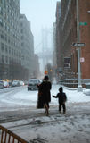 Blizzard of 2010 New York USA. Boxing Day 2010, mother and child on their way to a nearby sledding hill during a record blizzard that shrouds Manhattan Bridge as royalty free stock image