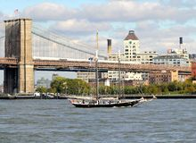 New York Brooklyn Bridge with Sailboat. This photo was taken in October, 2012 in New York City. The angle was taken from the Wall Street Heliport near sunset. A Stock Image