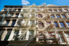 New York buildings facades with fire escape stairs, blue sky Stock Photos