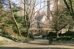 New York central park view. People on the bridge against NY skyscrapers royalty free stock image