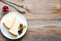 New York cheesecake or classic cheesecake with fresh berries on white plate. Wooden table background and copy space for text Royalty Free Stock Photo