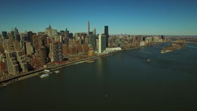 New York City Aerial. V59 Flying backwards over East River panning right with view of Manhattan and Long Island City cityscapes stock video