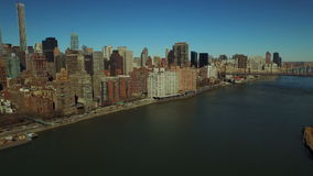 New York City Aerial. V43 Low flying over East River panning left with view of Midtown East Manhattan cityscape stock footage