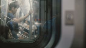 NEW YORK CITY AUG 18 2017 Atmospheric shot of passengers traveling in a subway train car seen blurred through windows.