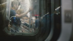 NEW YORK CITY AUG 18 2017 People traveling in a subway train car are seen blurred, reflected in windows during motion.