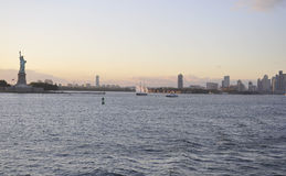 New York City,August 2nd:New Jersey City skyline and Statue of Liberty at sunset over Hudson river. New Jersey City skyline and Statue of Liberty at sunset over royalty free stock photo
