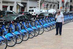 New York city bikes. NEW YORK, USA - JULY 2, 2013: Person walks by Citibike bicycle rental station in New York. With 330 stations and 6,000 bicycles it is one of Royalty Free Stock Photo