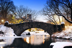 New York City Central Park bridge in winter. New York City Manhattan Central Park in winter with bridge over lake with snow, ducks and light at dusk Royalty Free Stock Image