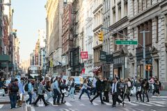 Busy crowds of people crossing New York City street. New York City 2018: Busy crowds of people walk across the intersection of Broadway and Spring Street in the stock photos
