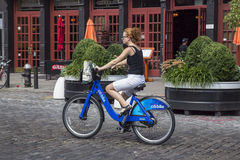 New York City Citibikes. Woman in New York City riding a public Citibike, an initiative of Mayor Michael Bloomberg Royalty Free Stock Images