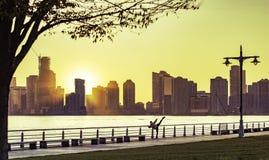 New York City, décembre 2015 : La femme sportive fait le yoga pendant que le soleil place au-dessus du pilier 45 sur Hudson River Photos stock