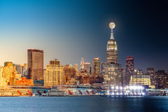New York City day to night timelapse. Composite day to night timelapse with the full moon rising above New York City skyline Stock Image
