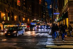New York City, East 46th Street, Manhattan - November 1, 2017: Street cars and pedestrians at night. Pedestrians crossing street near East 46th Street at night stock images