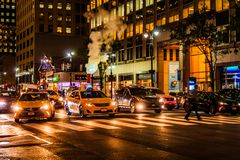 New York City, East 46th Street, Manhattan - November 1, 2017: Smoke pours out of manhole cover behind line of yellow cabs at nigh. T; street life near East 46th Royalty Free Stock Photo