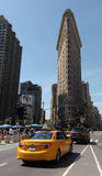 New York City, EUA: Construção do ferro de passar roupa com passagem amarela do táxi Imagem de Stock Royalty Free