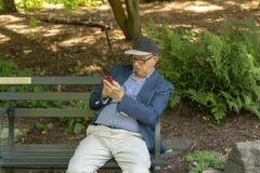 NEW YORK CITY, EUA - 26 DE JUNHO DE 2018: Homem adulto superior que texting ao descansar fora em um banco no parque imagens de stock royalty free