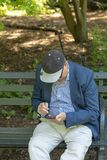 NEW YORK CITY, EUA - 26 DE JUNHO DE 2018: Homem adulto superior que texting ao descansar fora em um banco no parque imagem de stock