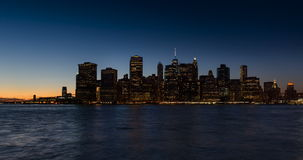 New York City Financial District and East River with passing boats at twilight
