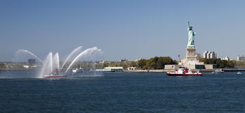 New York City Fire Department Boat and Statue of Liberty. New York, USA, SEPT 27, 2014: The New York City Fire Department Boat practices maneuvers  in the Hudson Royalty Free Stock Image
