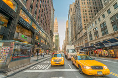 NEW YORK CITY - JUNE 8, 2013: Taxi speeds up along city street. Royalty Free Stock Photo