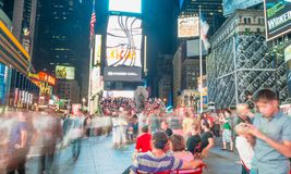 NEW YORK CITY - JUNE 15, 2013: Tourists in Times Square at night. New York attracts 50 million tourists every year Royalty Free Stock Photos
