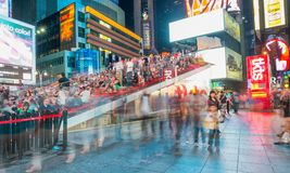 NEW YORK CITY - JUNE 15, 2013: Tourists in Times Square at night. New York attracts 50 million tourists every year Royalty Free Stock Image