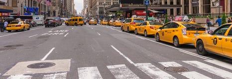 NEW YORK CITY - JUNI 13, 2013: Gula taxiar längs den Manhattan avenuen Arkivfoton