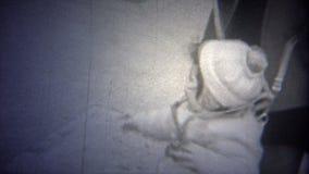NEW YORK CITY - 1946 : La maman a une laisse de harnais de protection de sécurité sur le bébé clips vidéos