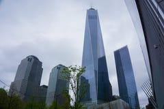 New York City, los E.E.U.U. - 1 de mayo de 2016: Casi acabado un World Trade Center y sitio conmemorativo adentro con el cielo az Imagen de archivo libre de regalías