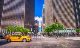 NEW YORK CITY - MAJ 24: Gula taxihastigheter upp längs stadsskyscrap Fotografering för Bildbyråer