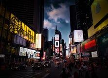 NEW YORK CITY MANHATTAN, APRIL, 24, 2015: Aftonsikten på byggnader för skärmar för NYC-Times Squareljus danar boutique ledde affi Arkivfoto