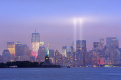 New York City Manhattan downtown night. New York City Manhattan downtown skyline at night with statue of liberty and light beams in memory of September 11 viewed Stock Image