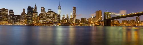 New York City Manhattan skyline at dusk. New York City Manhattan skyline panorama with Brooklyn Bridge and office skyscrapers building at dusk illuminated with Stock Photo