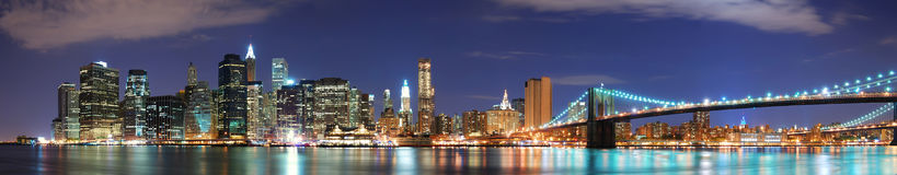 New York City Manhattan skyline panorama. With Brooklyn Bridge and office skyscrapers building in at dusk illuminated with lights at night