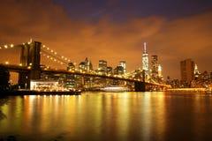 New York City Manhattan som är i stadens centrum med den Brooklyn bron på skymning Fotografering för Bildbyråer