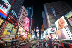 NEW YORK CITY - MARCH 12, 2018: Times Square is a busy tourist intersection of neon art and commerce and is an iconic street of Ma stock image